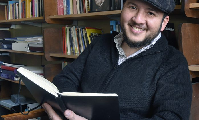 Oswaldo Estrada, holding his notebook, in his office in Dey Hall.